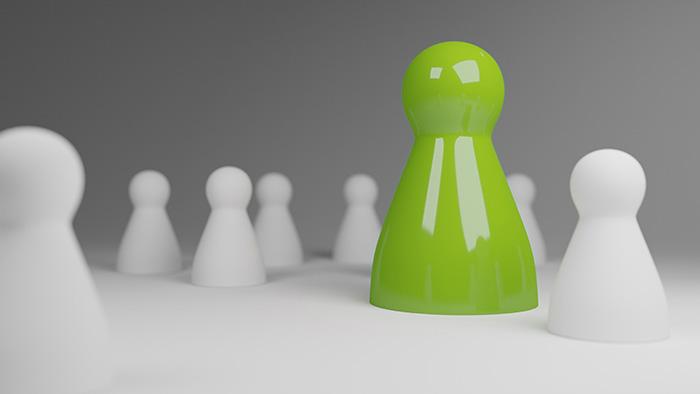 Eine grüne Spielfigur unter vielen weißen stellt symbolisch den Mehrwert dar